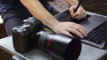 using stylus : Close up of creative photographer using graphic tablet for retouching. Close up of hands. Slider shot.