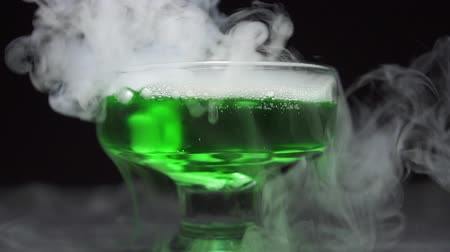 füstös : Magic potion is brewed in a glass bowl on a black background. Close-up, slow motion.