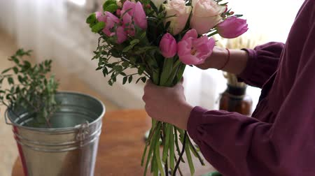narożnik : Woman florist makes bouquet of flowers in workshop, close up of hands