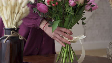 canto : Woman florist puts a bouquet on the table. Close-up.