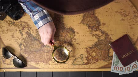 nagyító : Woman traveler examines a map of the world with a magnifier, top view. Travel concept.
