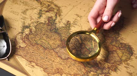 büyütmek : Woman traveler examines a map of the world with a magnifier, close up of hand. Slider shot. Stok Video