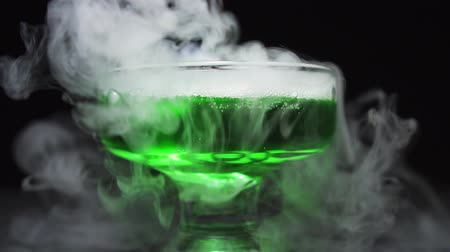 дополнение : Green liquid boils in a glass bowl, the chemical reaction of water to the addition of dry ice, close up.