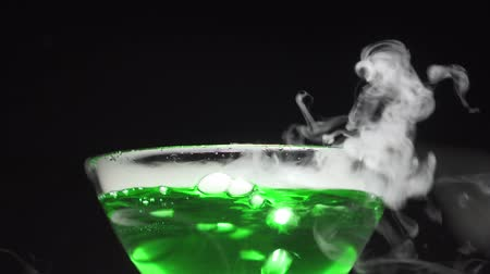 füstös : Green liquid boils in a glass bowl, a chemical reaction of dry ice to water. Side view.