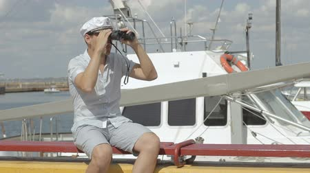 námořník : Sailor looking through the binoculars. The man is having fun on the waterfront. Captain against the sea with boats Dostupné videozáznamy