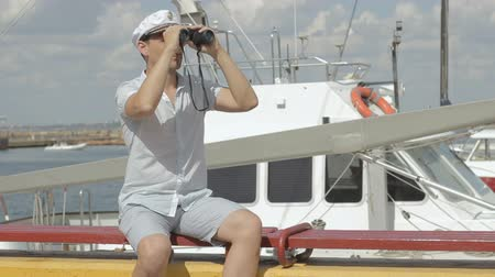námořník : Marine concept. Sailor looking through the binoculars. The man is having fun on the waterfront. Captain against the sea with boats Dostupné videozáznamy