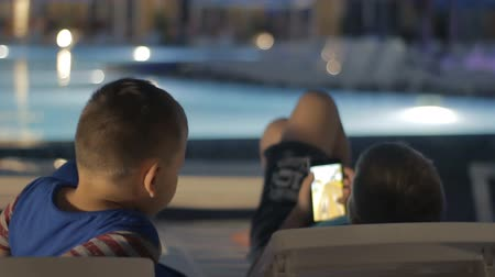 boyish : Young teenager playing game on smartphone. Children are entertained in the pool area online. Kids have digital fun
