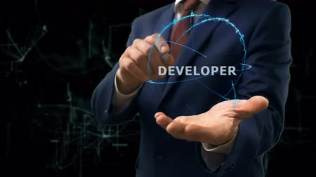 html : Businessman shows concept hologram Developer on his hand. Man in business suit with future technology screen and modern cosmic background