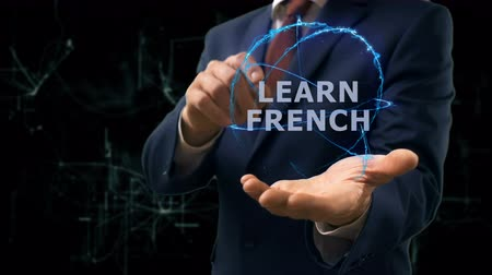 multilingual : Businessman shows concept hologram Learn French on his hand. Man in business suit with future technology screen and modern cosmic background
