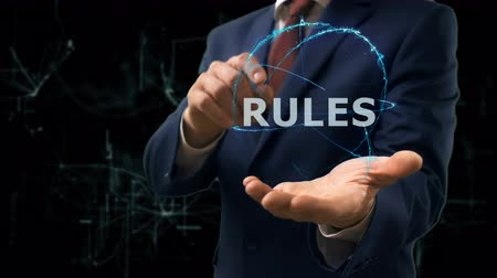 terms : Businessman shows concept hologram Rules on his hand. Man in business suit with future technology screen and modern cosmic background Stock Footage