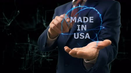 fabricated : Businessman shows concept hologram Made in USA on his hand. Man in business suit with future technology screen and modern cosmic background Stock Footage
