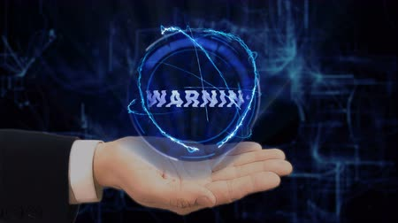 jelenleg : Painted hand shows concept hologram Warning on his hand. Drawn man in business suit with future technology screen and modern cosmic background Stock mozgókép