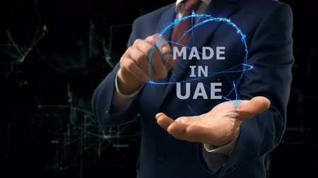 produced : Businessman shows concept hologram Made in UAE on his hand. Man in business suit with future technology screen and modern cosmic background