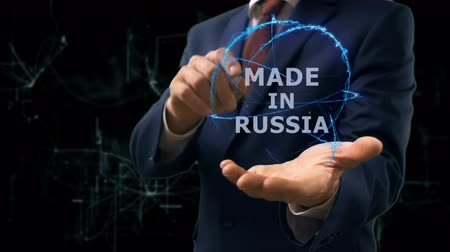 produced : Businessman shows concept hologram Made in Russia on his hand. Man in business suit with future technology screen and modern cosmic background