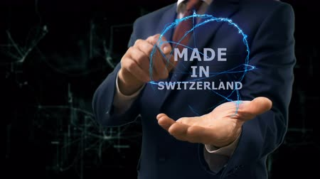 fabricated : Businessman shows concept hologram Made in Switzerland on his hand. Man in business suit with future technology screen and modern cosmic background Stock Footage