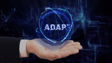 adapt : Painted hand shows concept hologram Adapt on his hand. Drawn man in business suit with future technology screen and modern cosmic background Stock Footage