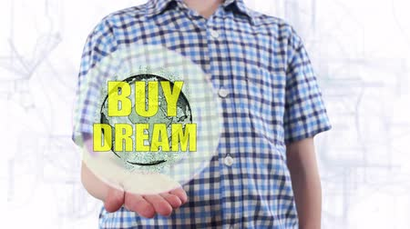 billing : Young man shows a hologram of the planet Earth and text Buy dream. Boy with future technology 3d projection on a modern white digital background