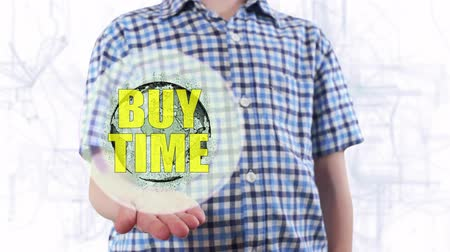 billing : Young man shows a hologram of the planet Earth and text Buy time. Boy with future technology 3d projection on a modern white digital background Stock Footage