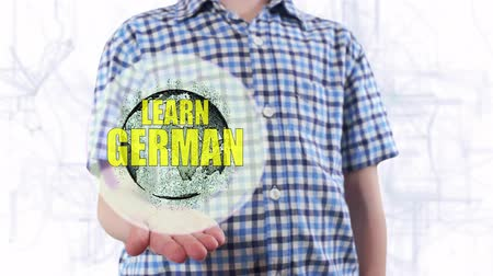 egyetem : Young man shows a hologram of the planet Earth and text Learn German. Boy with future technology 3d projection on a modern white digital background Stock mozgókép