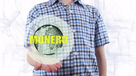 поколение : Young man shows a hologram of the planet Earth and text Monero. Boy with future technology 3d projection on a modern white digital background