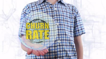 churn : Young man shows a hologram of the planet Earth and text Churn rate. Boy with future technology 3d projection on a modern white digital background