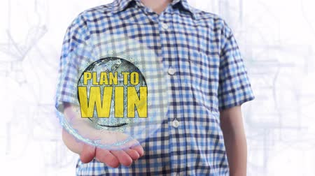gidermek : Young man shows a hologram of the planet Earth and text Plan to win. Boy with future technology 3d projection on a modern white digital background