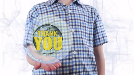 to you : Young man shows a hologram of the planet Earth and text Thank you. Boy with future technology 3d projection on a modern white digital background Stock Footage