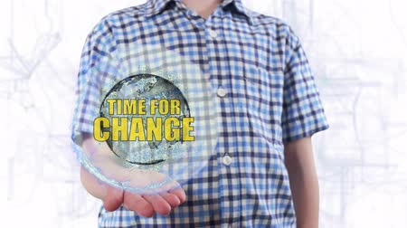 melhorar : Young man shows a hologram of the planet Earth and text Time for change. Boy with future technology 3d projection on a modern white digital background