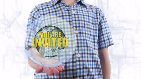 exclamação : Young man shows a hologram of the planet Earth and text You are invited. Boy with future technology 3d projection on a modern white digital background