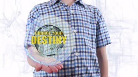 stratejik : Young man shows a hologram of the planet Earth and text Change your destiny. Boy with future technology 3d projection on a modern white digital background Stok Video