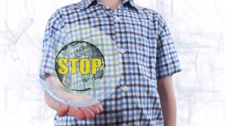haklar : Young man shows a hologram of the planet Earth and text Stop. Boy with future technology 3d projection on a modern white digital background