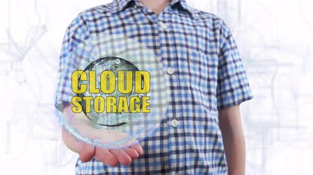 yöntem : Young man shows a hologram of the planet Earth and text Cloud storage. Boy with future technology 3d projection on a modern white digital background