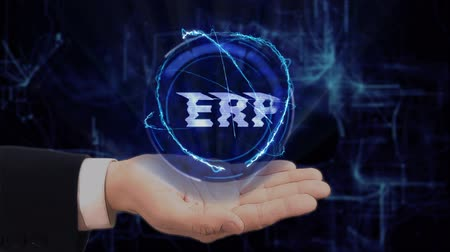 büro malzemesi : Painted hand shows concept hologram ERP on his hand. Drawn man in business suit with future technology screen and modern cosmic background Stok Video
