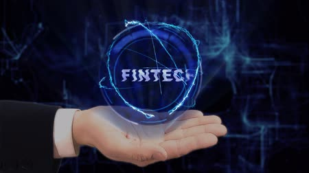 fintech : Painted hand shows concept hologram Fintech on his hand. Drawn man in business suit with future technology screen and modern cosmic background