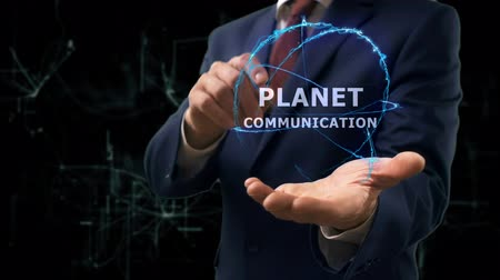 global iş : Businessman shows concept hologram Planet communication on his hand. Man in business suit with future technology screen and modern cosmic background