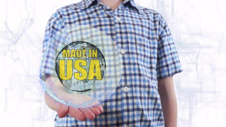 produced : Young man shows a hologram of the planet Earth and text Made in USA. Boy with future technology 3d projection on a modern white digital background Stock Footage