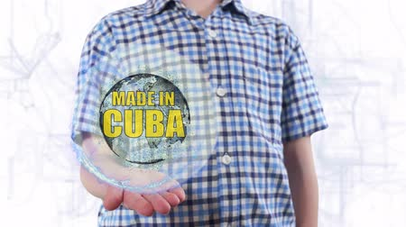 produced : Young man shows a hologram of the planet Earth and text Made in Cuba. Boy with future technology 3d projection on a modern white digital background