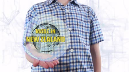 produced : Young man shows a hologram of the planet Earth and text Made in New Zealand . Boy with future technology 3d projection on a modern white digital background Stock Footage