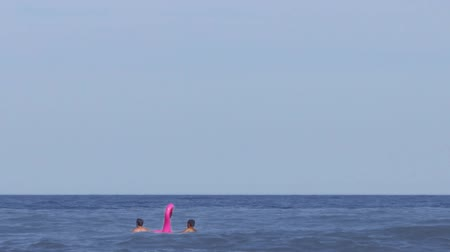 bóia : Children in the sea with an inflatable circle in the form of a pink flamingo. Active rest on the coast. Background for title or caption Vídeos