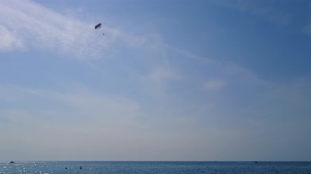 motorbot : Powerboat pulls a parachute in the sky. Parasailing in clear sunny weather. Marine entertainment. Active entertainment in the resort Stok Video