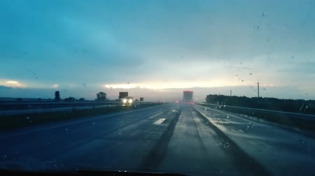 deštivý : A rainy sunset above the road. View through a wet windshield on the hightway