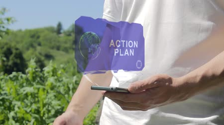motivasyonel : Man shows concept hologram Action plan on his phone. Person in white t-shirt with future technology holographic screen and green nature background