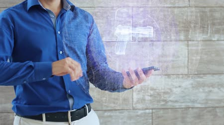defesa : Man activates a conceptual hologram with gun in the center. The guy in the blue shirt and light trousers with a holographic screen on the background of the wall