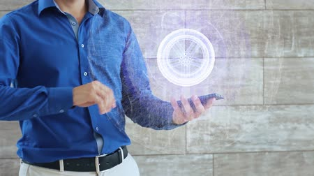 projeksiyon : Man activates a conceptual hologram with car wheel in the center. The guy in the blue shirt and light trousers with a holographic screen on the background of the wall Stok Video