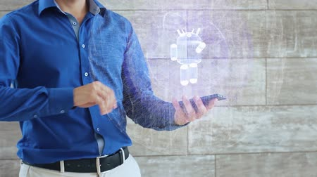 projeksiyon : Man activates a conceptual hologram with robot in the center. The guy in the blue shirt and light trousers with a holographic screen on the background of the wall