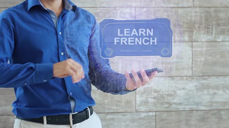 multilingual : Man activates a conceptual HUD hologram with text Learn French. The guy in the blue shirt and light trousers with a holographic screen on the background of the wall