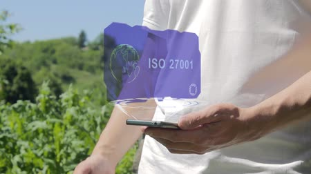 iso : Man shows concept hologram ISO 27001 on his phone. Person in white t-shirt with future technology holographic screen and green nature background