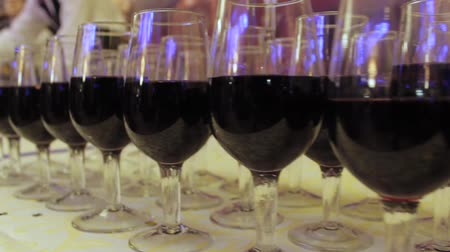 mais : The waiter pours wine into glasses at a party. On the table rows of glasses with red wine. Camera movement from left to right