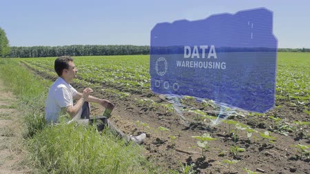 optimalizace : Man is working on HUD holographic display with text Data Warehousing on the edge of the field. Businessman analyzes the situation on his plantation. Scientist examines future technology