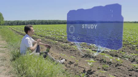 multilingual : Man is working on HUD holographic display with text Study on the edge of the field. Businessman analyzes the situation on his plantation. Scientist examines future technology